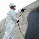 man sprays concrete foundation