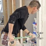 A man uses a roller to embed drywall tape when taping outside corner beads